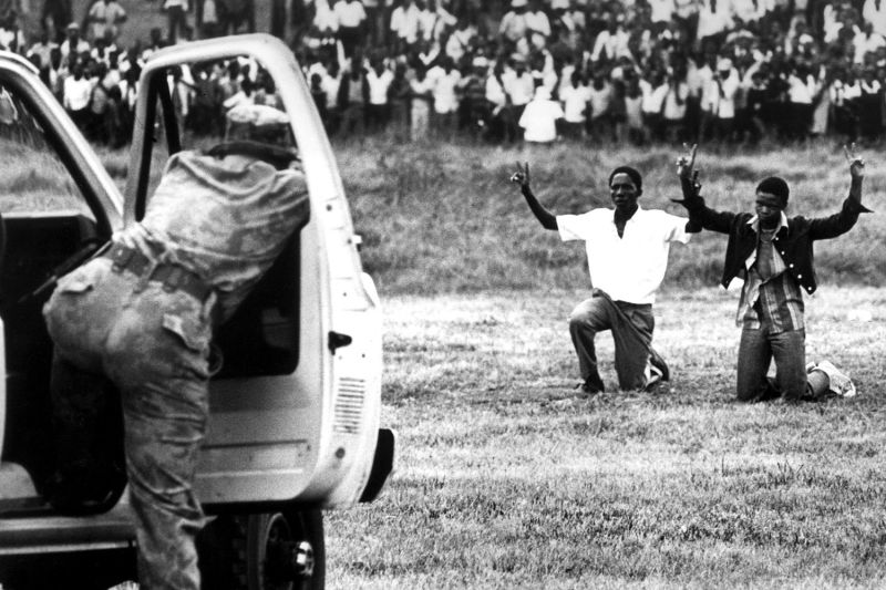 Youths kneel in front of police with their hands in the air during protests in Soweto, South Africa, on June 16, 1976.