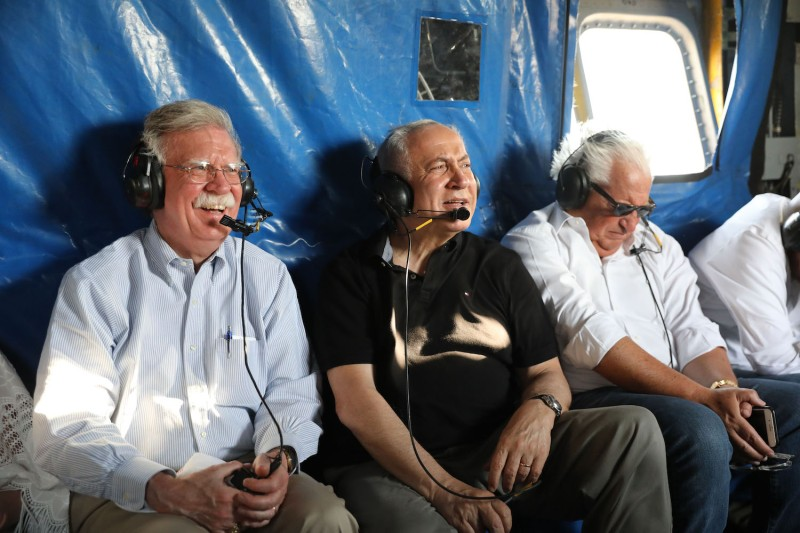 U.S. National Security Advisor John Bolton, Israeli Prime Minister Benjamin Netanyahu, and U.S. Ambassador to Israel David Friedman fly in a helicopter over the Jordan Valley on June 23, 2019.