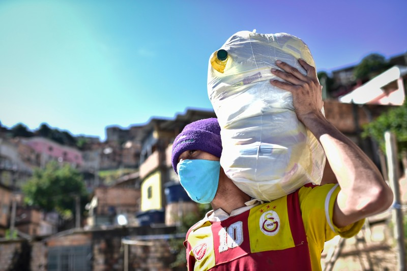 A resident of the Aglomerado da Serra Favela, carries food supplies on June 4, in Belo Horizonte, Brazil.