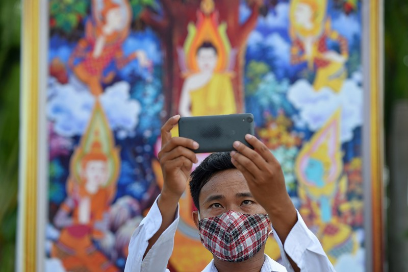 A man, wearing a face mask as a preventive measure against the spread of the coronavirus, poses for a selfie in front of a Buddha painting during the Visak Bochea Buddhist celebration in Phnom Penh on May 6.
