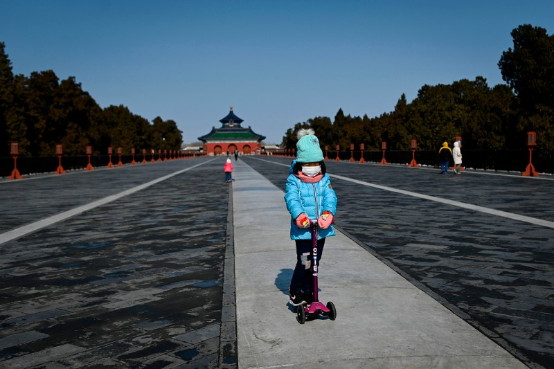A girl wearing a face mask plays on her scooter at a park in Beijing on Feb. 15.