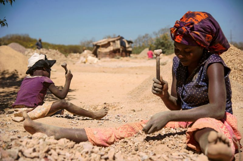 A child and a woman break rocks extracted from a cobalt mine in the Democratic Republic of the Congo