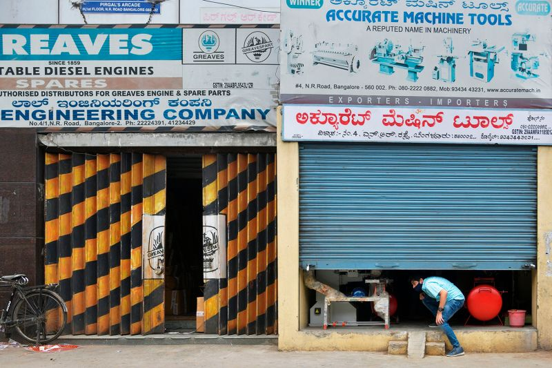 A trader shuts his shop in a commercial area closed by the authorities as coronavirus cases rise in Bengaluru on June 25.