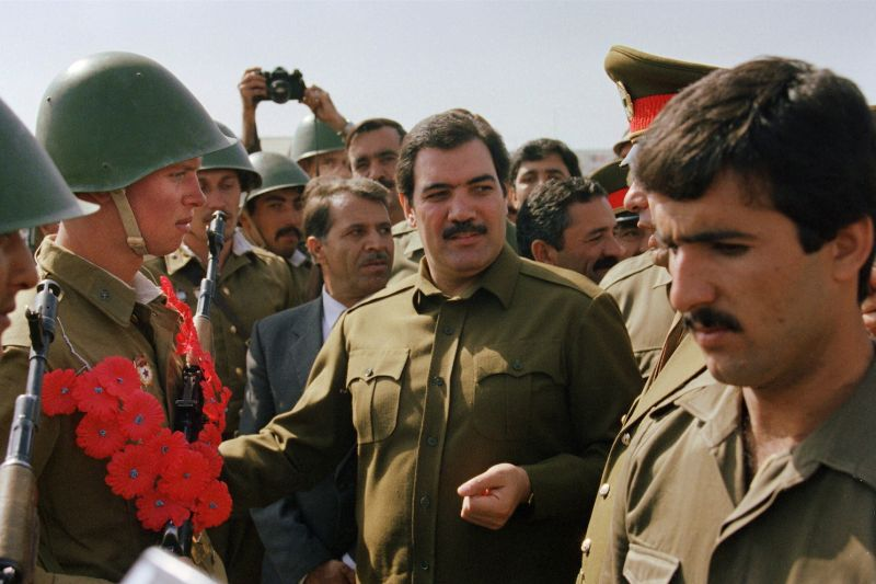 Then-Afghan President Mohammed Najibullah smiles as he meets Red Army soldiers.