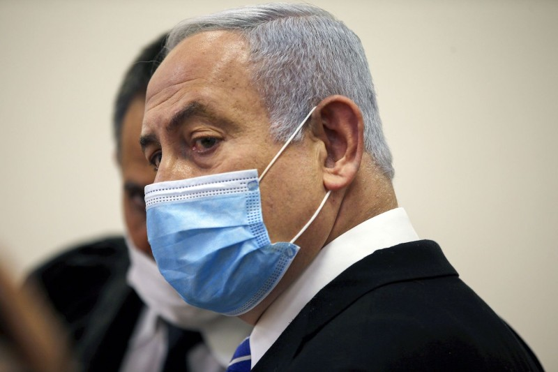 Israeli Prime Minister Benjamin Netanyahu wears a protective face mask inside a courtroom at the district court of Jerusalem on May 24, during the first day of his corruption trial.