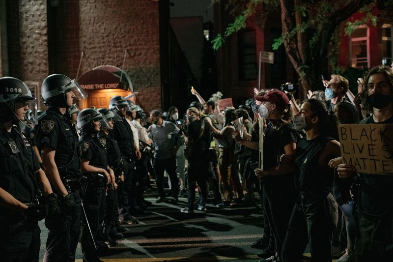 Demonstrators denouncing systemic racism in law enforcement face off with a line of NYPD officers hours after violating a citywide curfew on June 4 in New York City.