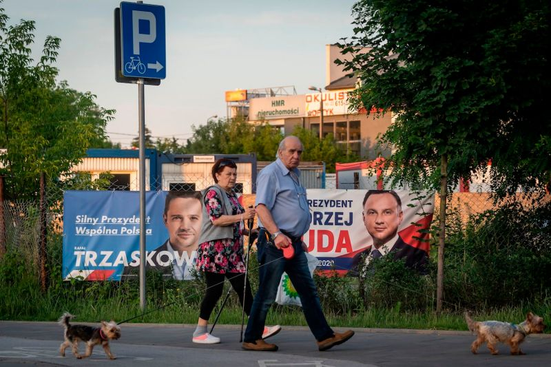 People walk their dogs as they pass by election posters of Polish President Andrzej Duda (R) and opposition candidate Rafal Trzaskowski (L) in a suburb of Warsaw, on June 25.