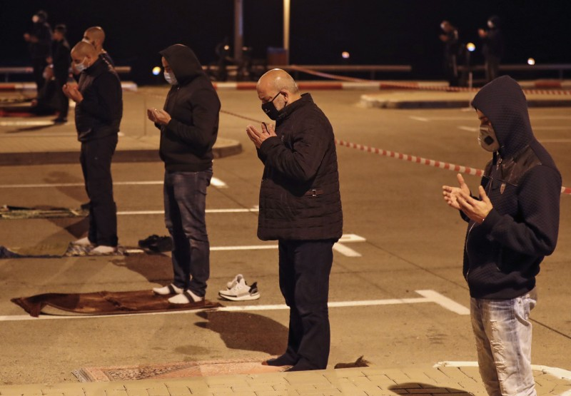 Palestinian and Arab- Israeli men practice social distancing amid the COVID-19 pandemic, as they pray in a parking lot near the beachin Jaffa, near Tel Aviv, after breaking their fast on the second day of Ramadan, on April 25.