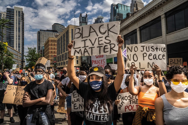Protesters wear facemasks and hold signs outside the Minneapolis 1st police precinct during a demonstration against police brutality and racism in Minnesota on June 13.