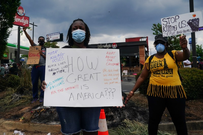 People hold signs toward traffic outside a burned Wendy's restaurant on the second day following the police shooting death of Rayshard Brooks in the restaurant parking lot June 14, 2020, in Atlanta, Georgia.
