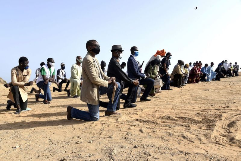Protesters wearing face masks kneel in Dakar, Senegal on June 9, during a rally in solidarity with the Black Lives Matter movement, and against racism and police brutality