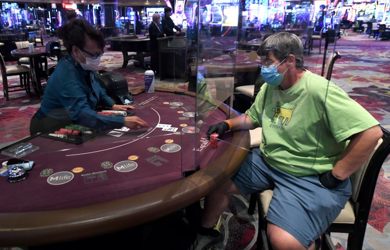 Nila Davis deals cards to Becky Lewis of Texas at a blackjack table with plexiglass safety shield dividers at Excalibur Hotel & Casino on June 11, 2020 in Las Vegas, Nevada.