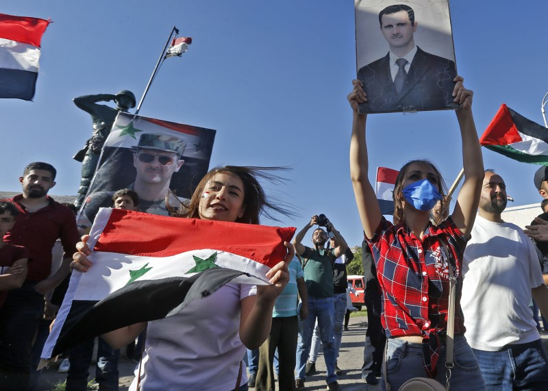 People wave Syrian national flags and pictures of President Bashar al-Assad during a demonstration against U.S. in Damascus on June 11.