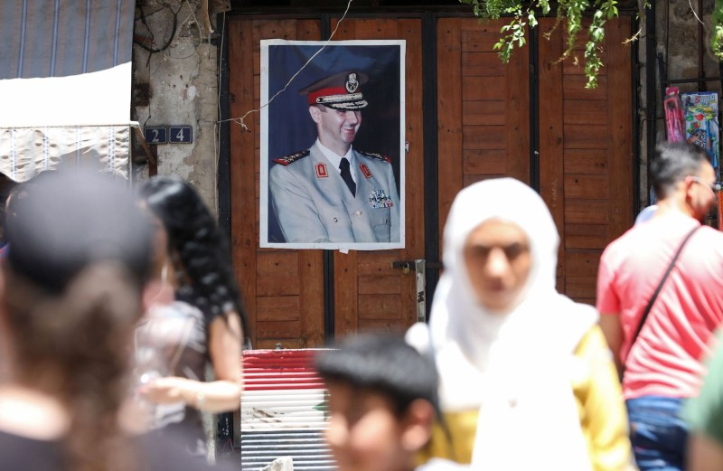 A portrait of Syrian President Bashar al-Assad hangs in old Damascus, Syria, on June 16, 2020.