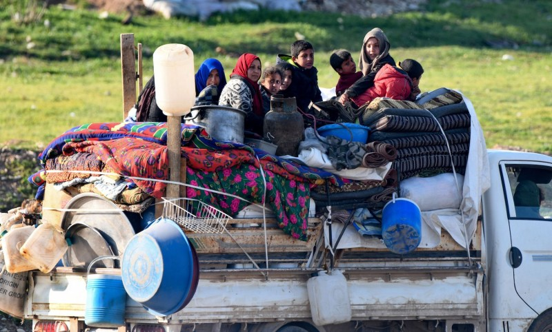 Syrians displaced by pro-regime strikes, join a convoy driving toward the Deir al-Ballut checkpoint in Syria on April 11, 2020.