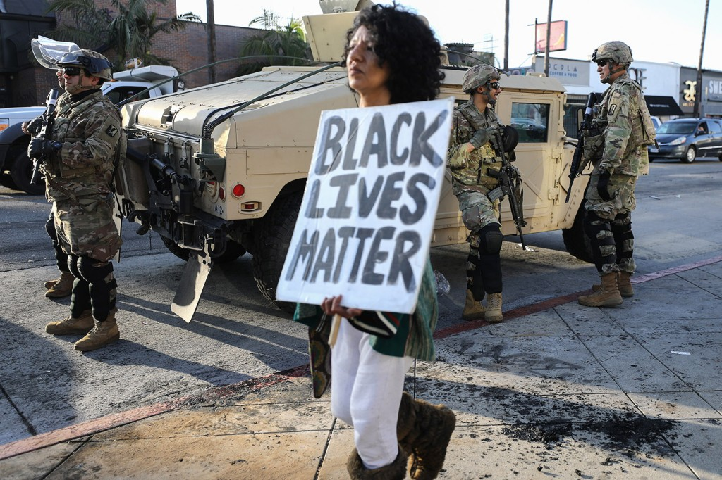 "A woman carries a ""Black Lives Matter"" sign past U.S. National Guard troops in the Fairfax District of Los Angeles, which was damaged during unrest after George Floyd, a black man, was killed by a white police officer in Minneapolis."