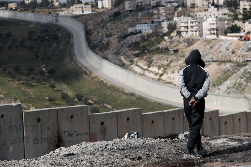 A young Palestinian walks along Israel's controversial wall in the occupied West Bank Palestinian village of Abu Dis on Jan. 29.