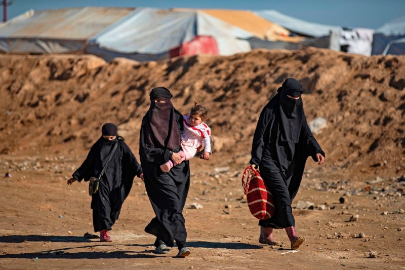 Women and children walk inside the Kurdish-run al-Hol camp in northeastern Syria on Jan. 14, where families of Islamic State foreign fighters are held.