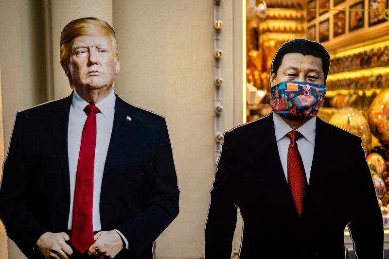 Cardboard figures of U.S. President Donald Trump and Chinese President Xi Jinping wearing a face mask stand in front of a souvenir shop in Moscow on June 3.