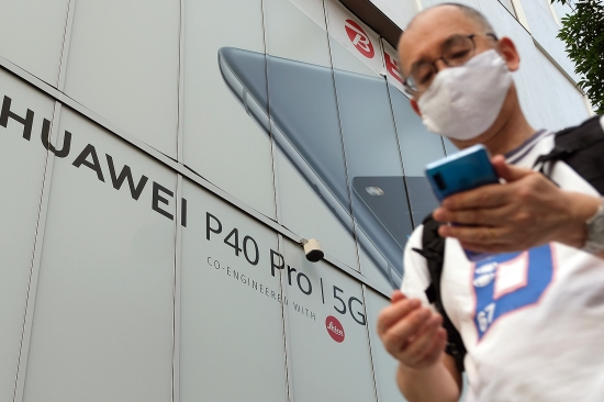 A pedestrian walks under an advertisement for the Chinese telecommunications company Huawei's latest phone in Tokyo on June 26. The Trump administration has taken actions to limit Chinese companies' access to American markets or technology, most notably by banning Huawei from the American 5G market.