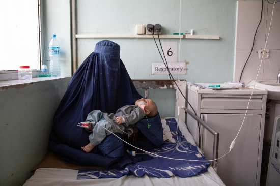 A woman holds her child in the pediatric department at Mirwais Hospital on Feb. 17. This is the third hospitalization for the 2-year-old, who suffers from malnutrition.