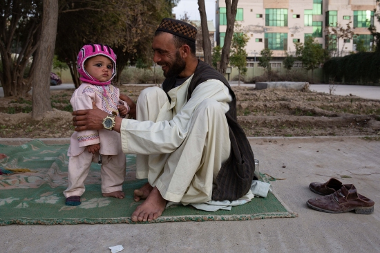 A father and son wait outside the maternity ward at Mirwais Hospital on Feb. 17.