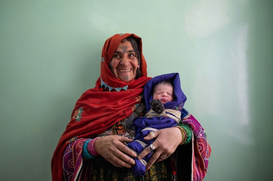 A proud grandmother holds a newborn baby boy after he received his vaccinations in the maternity ward at Mirwais Hospital on Feb. 18.