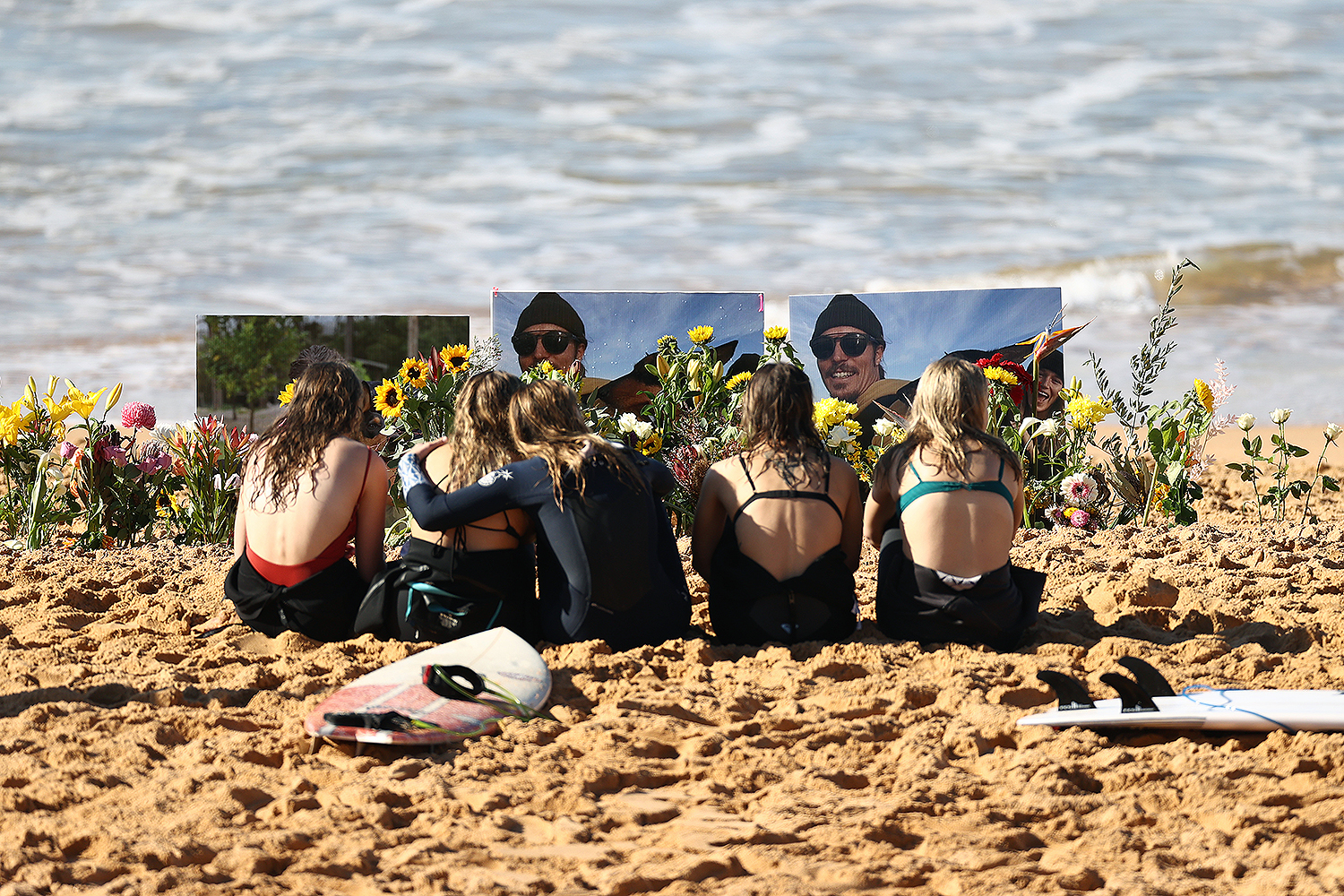 "Friends pay their respects to Australian Olympic snowboarder Alex ""Chumpy"" Pullin at North Narrabeen Beach in Sydney on July 12. Pullin died in a drowning accident while spearfishing at the age of 32. Ryan Pierse/Getty Images"
