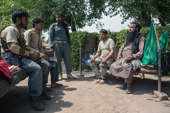 Anar Gul (far right) sits with other police officers at his front-line checkpoint in Nangarhar's Surkhrod district in Afghanistan on June 24.