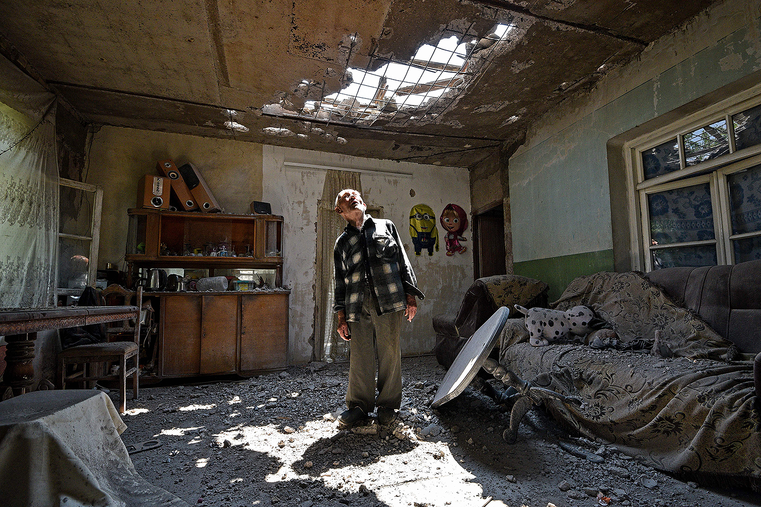 Aram Vardazaryan stands inside his home in the village of Aygepar, Armenia, on July 18 after it was hit by shelling during armed clashes on the Armenian-Azerbaijani border. Russia said it is prepared to mediate peace talks between ex-Soviet rivals Armenia and Azerbaijan after fighting escalated. KAREN MINASYAN/AFP via Getty Images