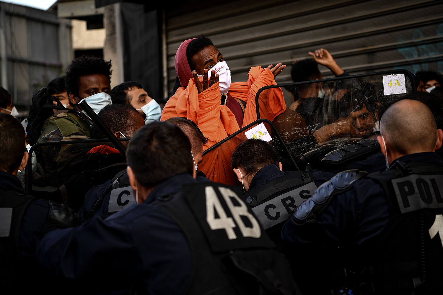 Asylum seekers face riot police officers during their evacuation from a makeshift camp in Aubervilliers, France, on July 29. CHRISTOPHE ARCHAMBAULT/AFP via Getty Images