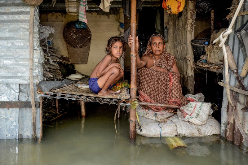 "A woman and a young girl sit in their flooded house in Sunamganj, Bangladesh, on July 16. Al Jazeera reported that ""a third of Bangladesh is underwater"" after some of the worst flooding in a decade. MUNIR UZ ZAMAN/AFP via Getty Images"