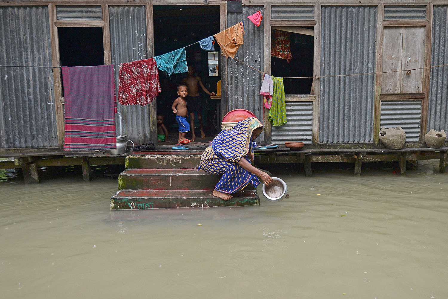 A woman washes her cooking pot in the floodwaters outside her house in Sreenagar, Bangladesh, on July 20. MUNIR UZ ZAMAN/AFP via Getty Images