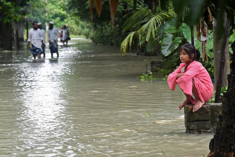 A girl sits alongside a flooded walkway in Sreenagar, Bangladesh, on July 20. MUNIR UZ ZAMAN/AFP via Getty Images