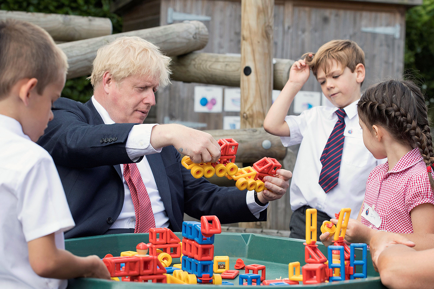 British Prime Minister Boris Johnson plays with children during a visit to The Discovery School in Kings Hill, England, on July 20. JEREMY SELWYN/POOL/AFP via Getty Images