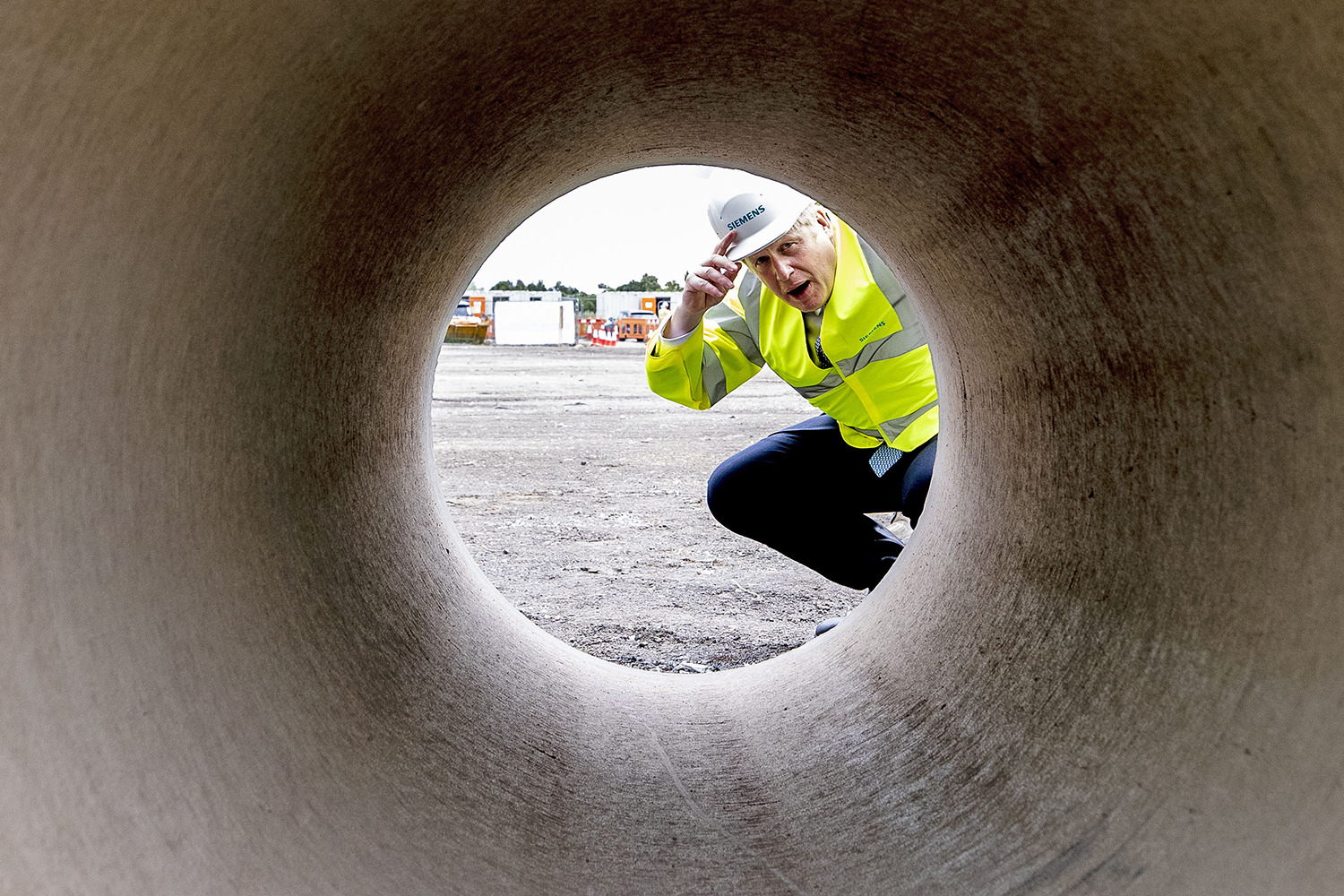 Prime Minister Boris Johnson looks through a large bore pipe during a visit to the Siemens Mobility rail factory construction site in Goole, England, on July 6. Peter Byrne/WPA Pool/Getty Images