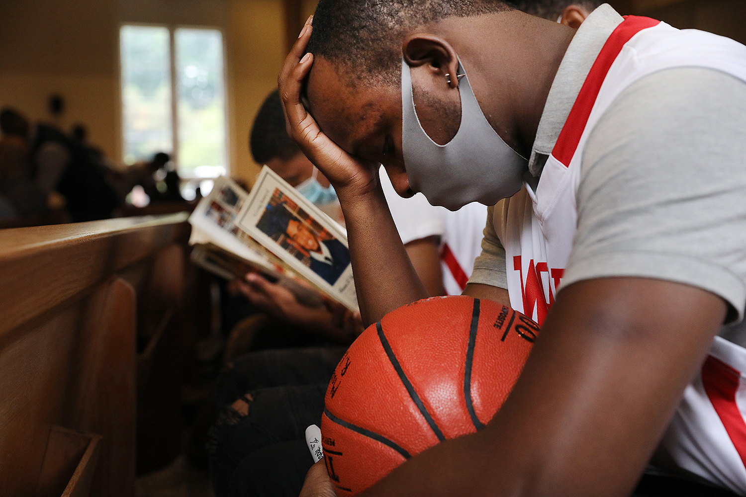 Isaiah Campbell bows his head at a funeral in Bronxville, New York, on July 15 for his friend and former teammate Brandon Hendricks-Ellison, a young basketball star who was fatally shot in the Bronx just days after graduating from high school. Spencer Platt/Getty Images