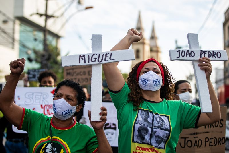 Protesters hold crosses bearing the names of victims—including that of João Pedro, 14, who was killed at home by police in May—in the streets of São Gonçalo, Brazil, on June 5.