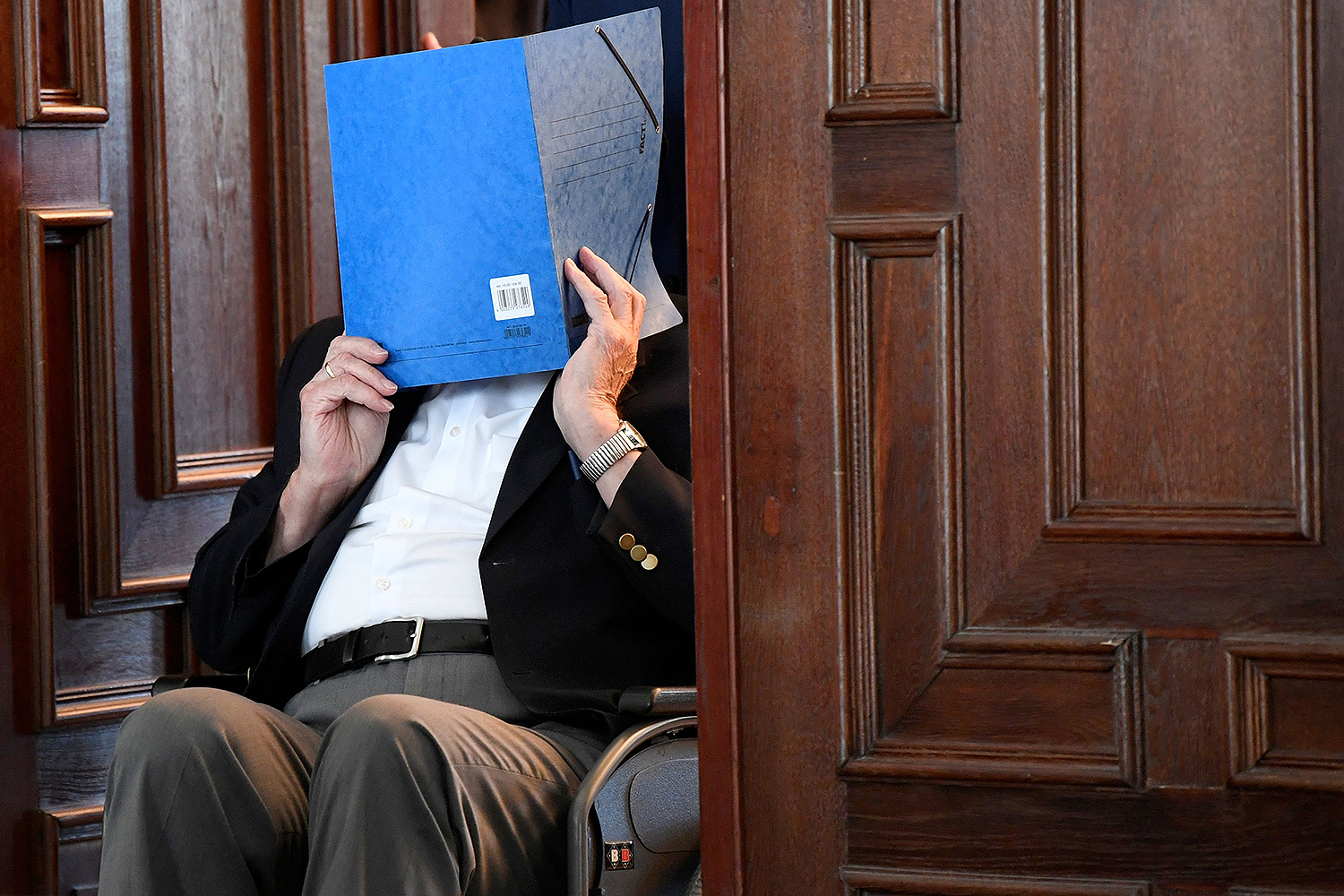 Bruno Dey, a former SS watchman at the Stutthof concentration camp, hides his face behind a folder as he leaves in a wheelchair after the verdict in his trial in Hamburg, Germany, on July 23. The 93-year-old former Nazi concentration camp guard was handed a suspended sentence of two years in prison as the court found him guilty of complicity in World War II atrocities. FABIAN BIMMER/POOL/AFP via Getty Images