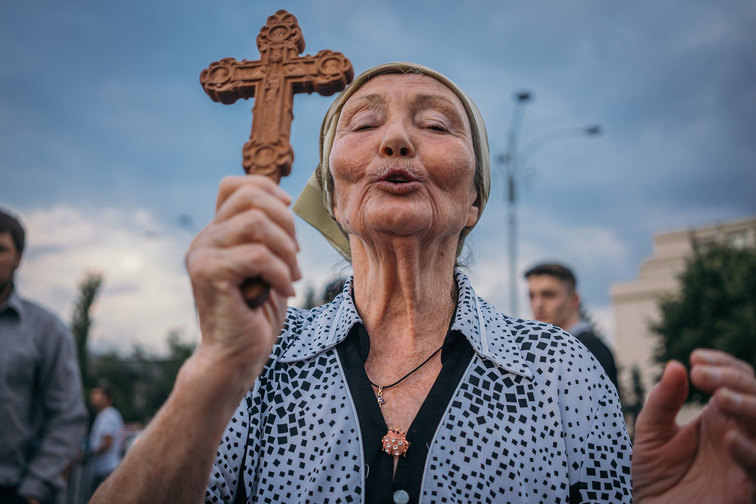 A woman prays during a protest against the Romanian government and its coronavirus measures in Bucharest on July 12. ANDREI PUNGOVSCHI/AFP via Getty Images