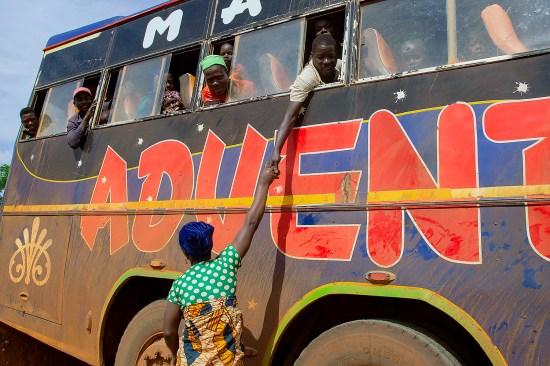 Ntahombaye Melania reaches up to greet her husband, Misago Alexis, who fled political violence in Burundi in 2015, as he returns to the Gisuru border post in Ruyigi, Burundi, on Oct. 3, 2019.