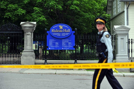 A Canadian police officer walks by Rideau Hall near the grounds of the Ottawa estate that is home to Prime Minister Justin Trudeau and the country's governor general on July 2, following the arrest of an armed man who entered the grounds.
