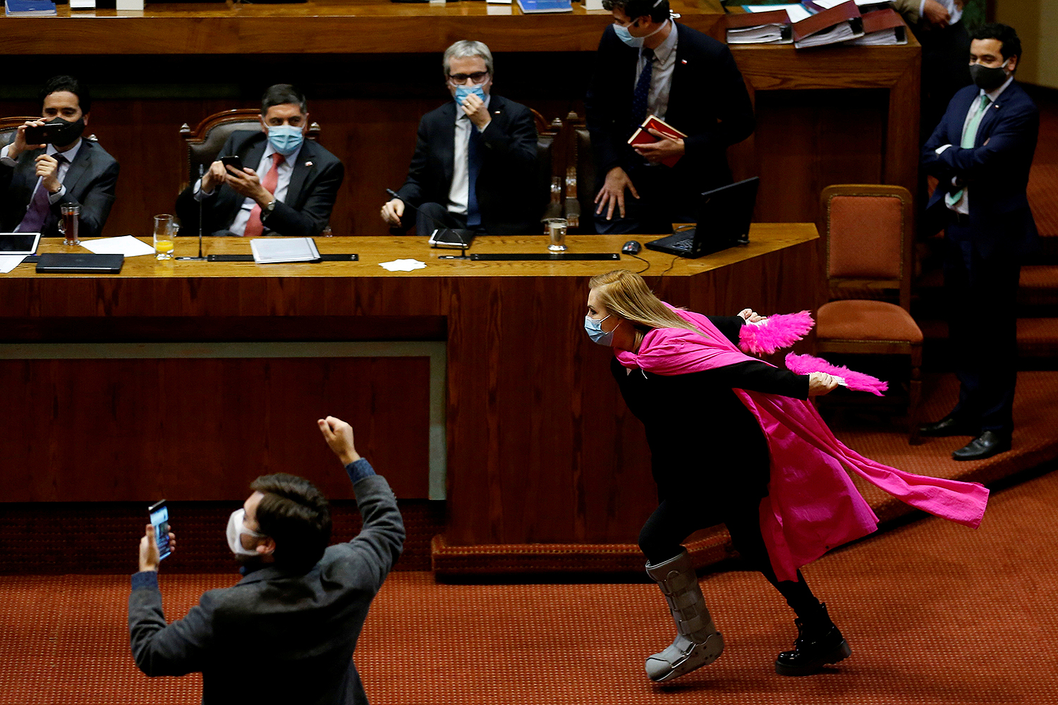 Chilean lawmaker Pamela Jiles runs through congress wearing a pink cape and waving matching fans to celebrate passage in the lower house of a coronavirus emergency aid measure in Valparaiso, Chile, on July 15. Rodrigo Garrido/REUTERS