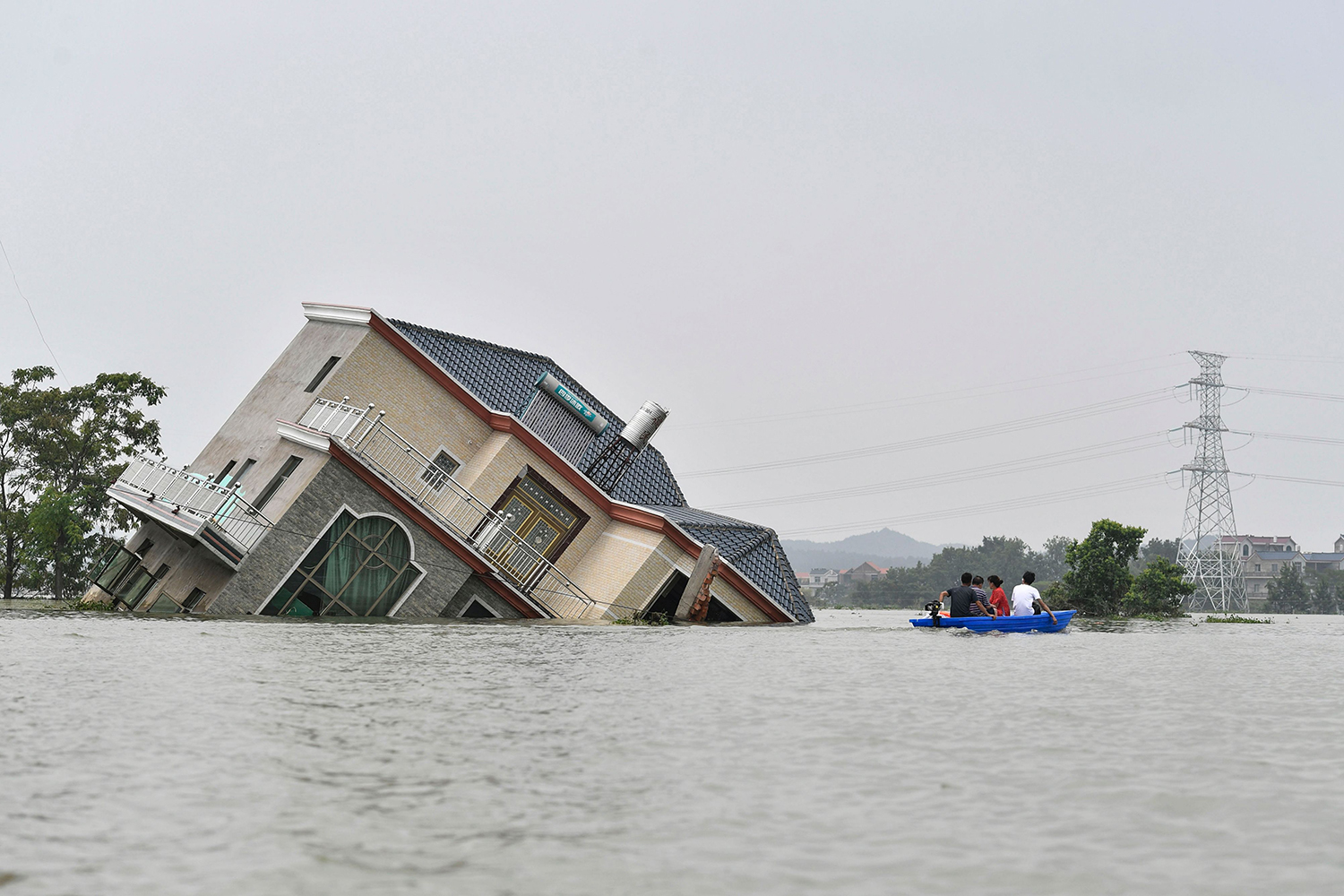Residents ride past a flood-destroyed house near the Poyang Lake in China's central Jiangxi province July 15. STR/AFP via Getty Images