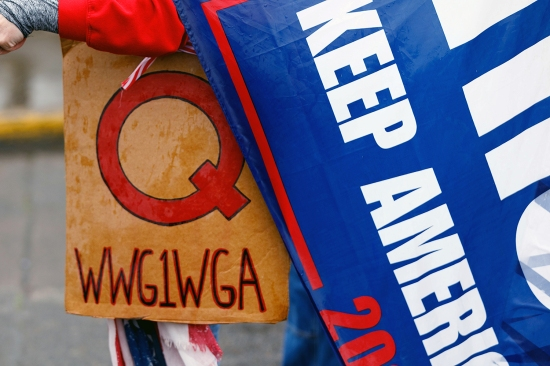 A QAnon conspiracy theorist holds a WWG1WGA sign and Donald Trump banner during a protest at the Oregon State Capitol in Salem on May 2.