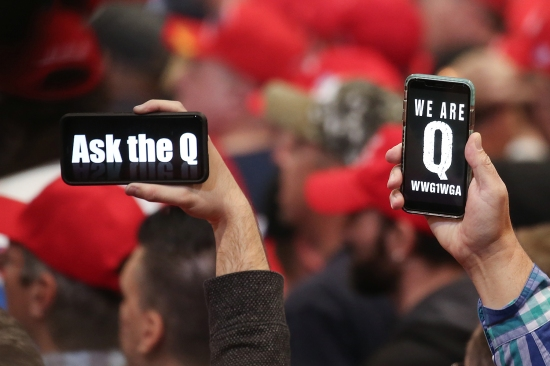 Trump supporters hold up their phones with messages referring to the QAnon conspiracy theory at a campaign rally in Las Vegas on Feb. 21.