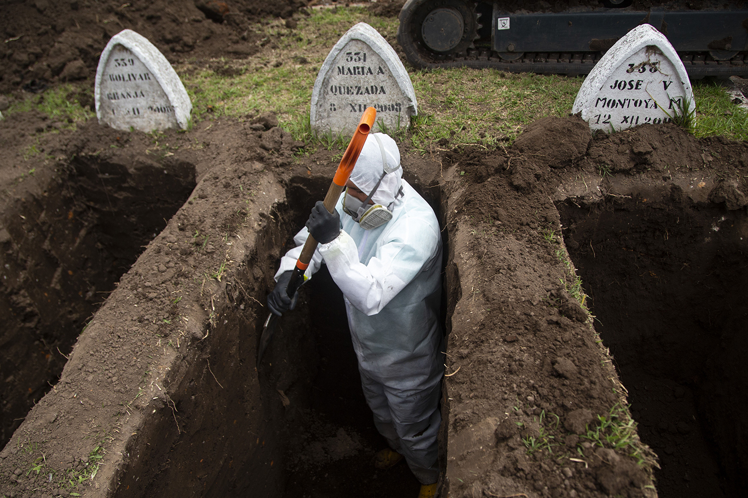 A worker wearing biosecurity equipment digs graves for coronavirus victims at the San Diego Cemetery in Quito, Ecuador, on July 21. CRISTINA VEGA RHOR/AFP via Getty Images