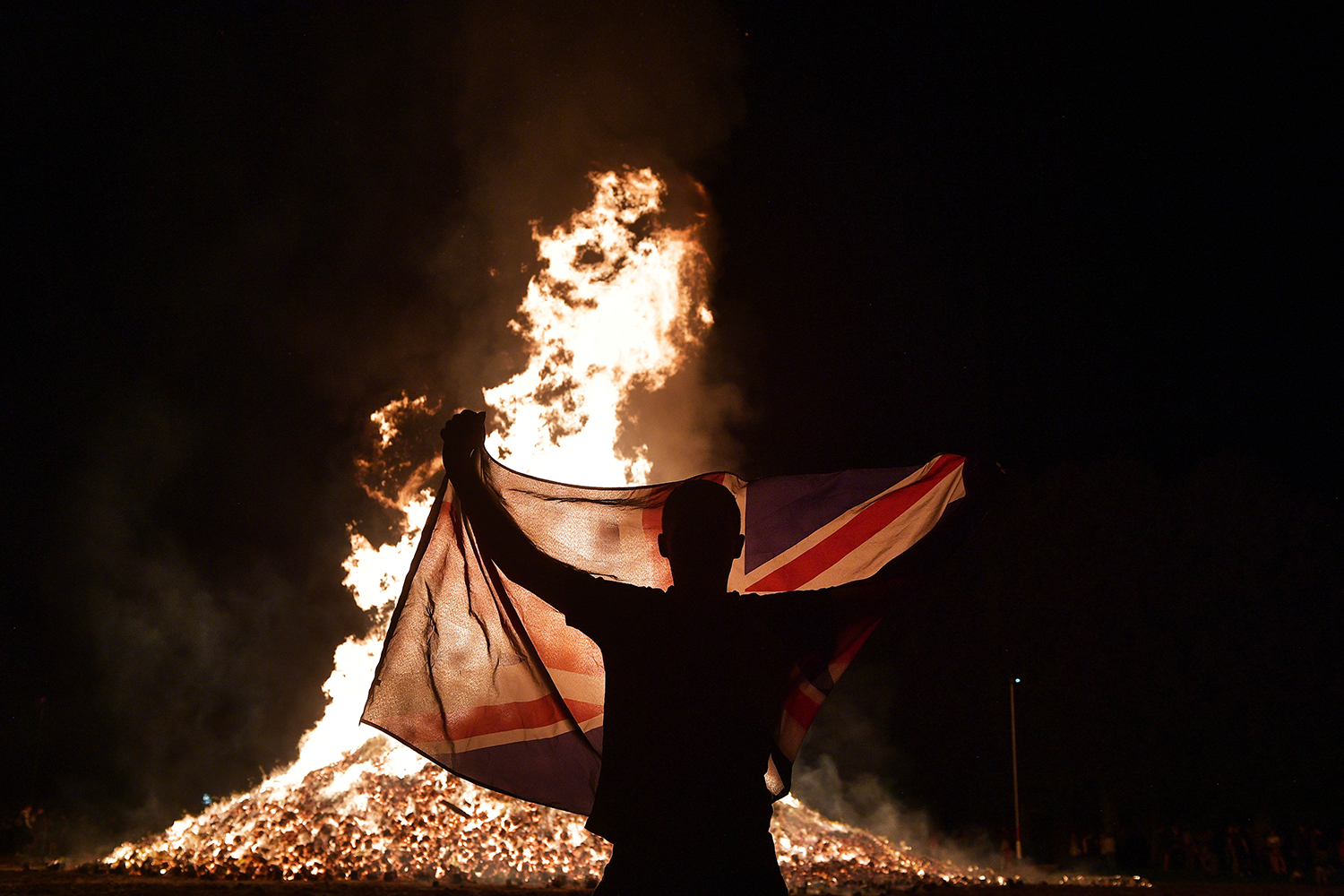 A loyalist waves a Union Jack flag at the Ballycraigy estate's Eleventh Night bonfire in Antrim, Northern Ireland, on July 11. Loyalists traditionally light bonfires at the stroke of midnight to signal the beginning of the Twelfth of July, which marks the victory of the Protestant King William of Orange over the Catholic King James II at the Battle of the Boyne in 1690. Charles McQuillan/Getty Images