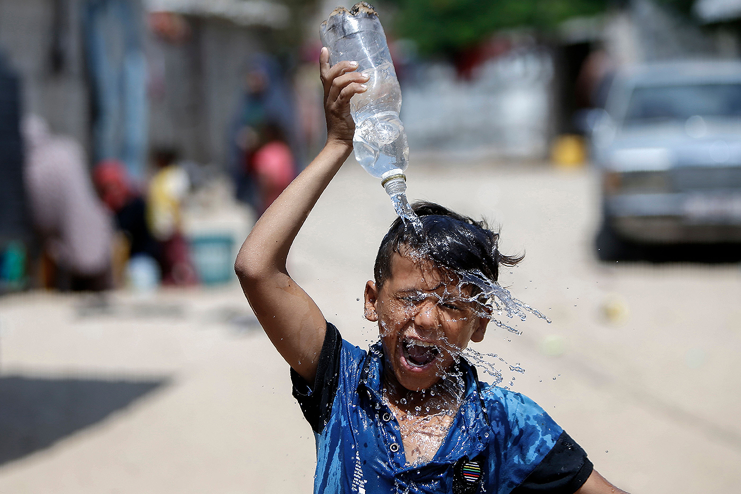 A Palestinian boy pours water over his head in Khan Yunis in the southern Gaza Strip on July 22. MOHAMMED ABED/AFP via Getty Images