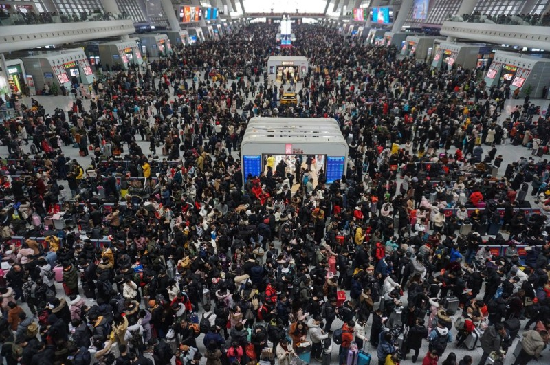 Crowds of travelers walk through a hall at a railway station in Hangzhou in China's eastern Zhejiang province on the last day of the Spring Festival holiday on Feb. 10, 2019.